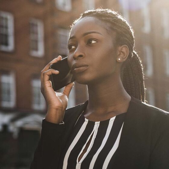 Young black woman using the phone while standing outside